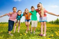Дети обнимая стоять в поле Стоковые Изображения