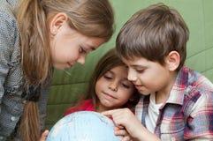 Дети смотря глобус Стоковые Фото