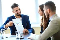 Деловые партнеры обсуждая документы и идеи на встрече Стоковые Изображения RF
