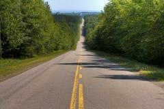 Длинная прямая дорога через холмистый ландшафт Стоковые Фотографии RF