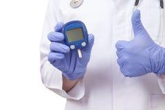 Доктор держа метр уровня сахара в крови. Показывать ОДОБРЕННЫЙ знак Стоковые Изображения