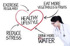 Доктор показывая здоровый образ жизни Стоковые Изображения