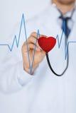 Доктор слушая к сердцебиению Стоковые Изображения