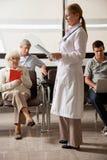 Доктор Чтение Хранить С Люди в лобби Стоковое Фото