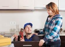 Домохозяйка наблюдая как работник ремонтируя водоразделы Стоковые Изображения