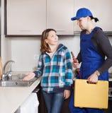 Домохозяйка наблюдая как работник ремонтируя водоразделы Стоковые Фото