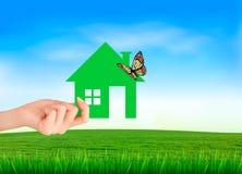 Дом в руке на зеленой естественной предпосылке Стоковые Изображения