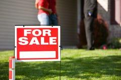 Дом: Для продажи знак с агентом и пары внутри подпирают Стоковое Изображение