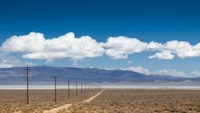 Дорога пыли с опорами линии электропередач в сторону Стоковые Изображения