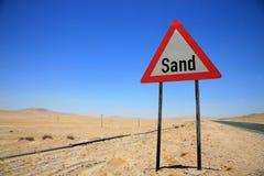 Дорожный знак опасности песка в Намибии Стоковые Фото