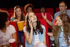 Досадная женщина на телефоне во время кино Стоковые Фотографии RF