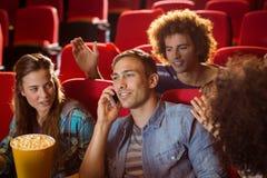 Досадный человек на телефоне во время кино Стоковое фото RF