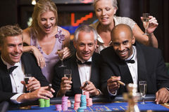 друзья играя в азартные игры таблица рулетки группы Стоковое фото RF