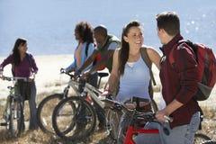 Друзья при велосипед смотря один другого Стоковые Изображения