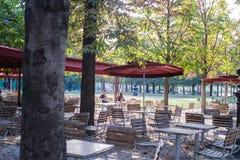 Друзья сидят на таблице кафа в Tuileries, Париже, Франции Стоковое Изображение