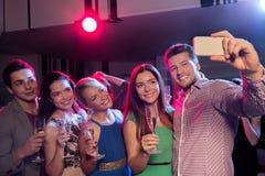 Друзья с стеклами и smartphone в клубе Стоковая Фотография