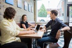 Друзья тратя часы досуга в кафе Стоковая Фотография