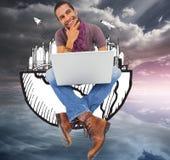 Думая человек сидя на поле используя компьтер-книжку и усмехаться Стоковое Изображение RF