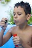 дуя пузыри мальчика Стоковое Фото