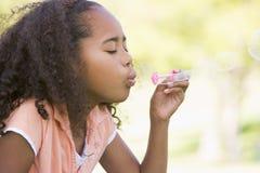 дуя детеныши девушки пузырей outdoors Стоковое фото RF