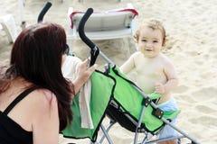 婴儿坐的微笑的婴儿推车 免版税库存照片