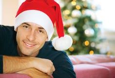 戴圣诞老人的帽子的年轻人 免版税图库摄影