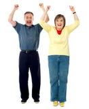 兴奋高级夫妇。 被举的胳膊 库存图片