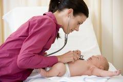 婴孩产生听诊器的核对医生 免版税库存照片
