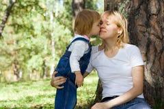 婴孩亲吻保姆 库存图片