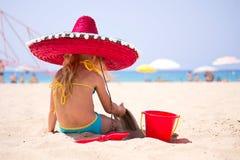 婴孩坐在一个红色帽子的海滩 免版税库存图片