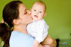 婴孩她的亲吻母亲 库存照片