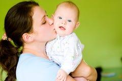 婴孩她的亲吻母亲 免版税库存图片
