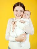 婴孩她的在黄色的母亲 免版税库存图片