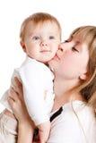 婴孩愉快的亲吻母亲 库存图片
