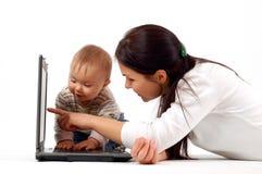 婴孩有乐趣的女孩膝上型计算机母亲 免版税库存图片