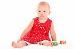 婴孩美丽的叮咬女孩嘴唇鹳较大 免版税图库摄影