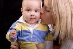 婴孩美丽的面颊亲吻的妈妈年轻人 免版税库存图片