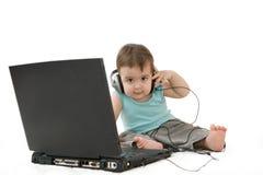 婴孩膝上型计算机和耳机 图库摄影