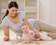 婴孩阻拦母亲使用木 免版税库存照片