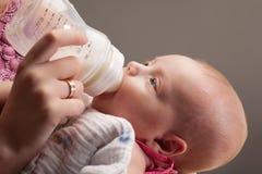 婴孩饮用的女孩牛奶 免版税图库摄影