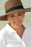 戴布朗夏天帽子的可爱的妇女 免版税库存图片