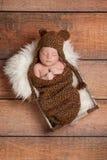 戴熊帽子的休眠的新出生的男婴 免版税库存图片