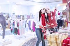 购物与台车的愉快的朋友在购物中心 免版税库存图片