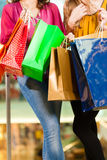 购物与在购物中心的袋子的二名妇女 免版税图库摄影