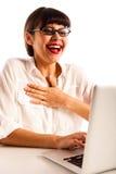 戴眼镜的妇女,惊奇和愉快在膝上型计算机 库存照片