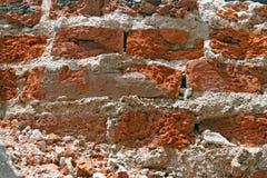 崩裂红色墙壁的砖 库存照片