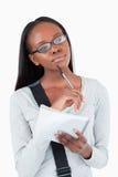 戴记事本和眼镜的少妇在想法 库存图片