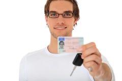 年轻人显示他的驾驶执照和汽车关键字 免版税库存照片