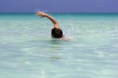 年轻人游泳在海运 免版税库存图片