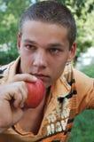 年轻人用红色苹果 图库摄影